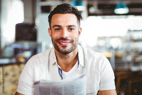 Fototapety, obrazy:  Young man having cup of coffee reading newspaper