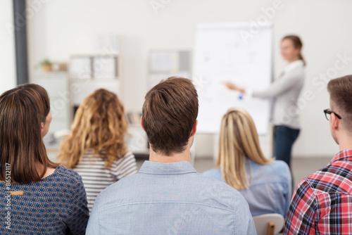 Foto  Frau Hält EINEN vortrag am Flipchart Vor einer Gruppe