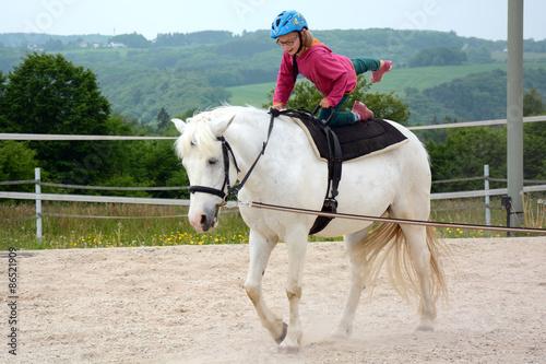 Papiers peints Equitation Mädchen bei Reitunterricht in Reitschule macht Kunststücke beim Pferdereiten