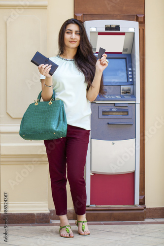 Photo  Young woman in jeans short using an automated teller machine