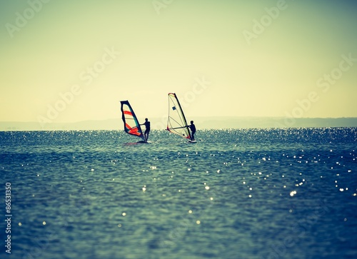 fototapeta na ścianę Windsurfers swimming in sea.