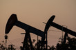 Oil drilling pumpjack silhouette during sunset pumping crude oil during crisis, orange grey background