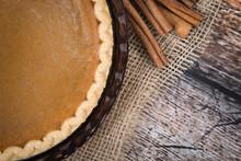 Pumpkin Pie With Cinnamon Sticks On Wooden Vintage Table