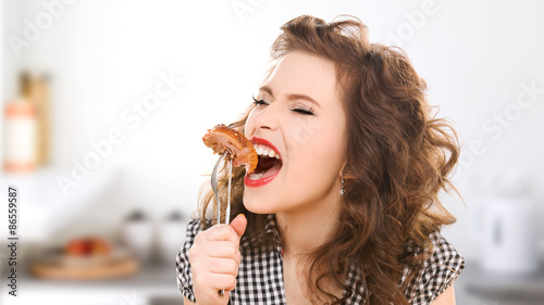 Valokuva  hungry young woman eating meat on fork in kitchen