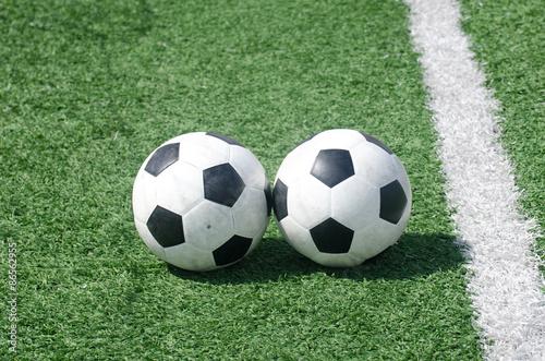 Vászonkép footballs soccer on green grass field