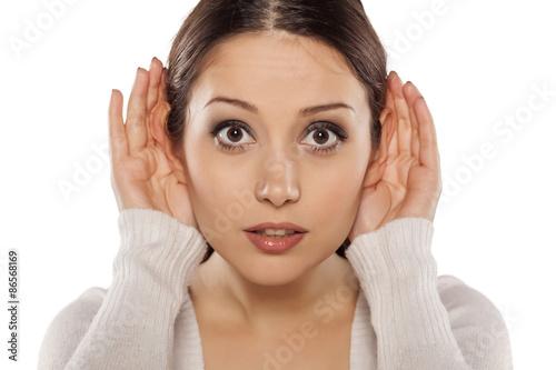 Foto  Junge Frau, die sorgfältig mit ihren Händen hinter den Ohren hört