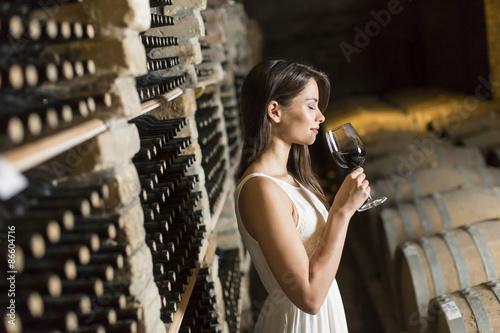 Leinwand Poster Junge Frau im Weinkeller