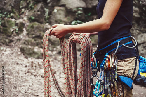 Foto auf Leinwand Bergsteigen Woman holding climbing rope near the rock