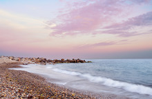 Sea And The Pebble Beach Under The Sunset Sky