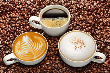 Fototapeta Kawa Variety of cups of coffee on coffee beans background