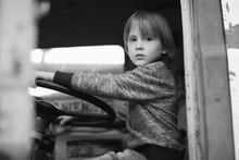 Cute Boy Portrait Sitting In A Driver Seat