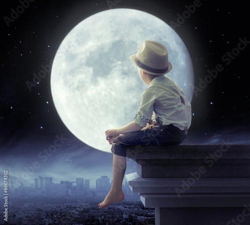 chlopiec-w-kapeluszu-patrzacy-na-puste-miasto-noca-na-tle-pelni-ksiezyca