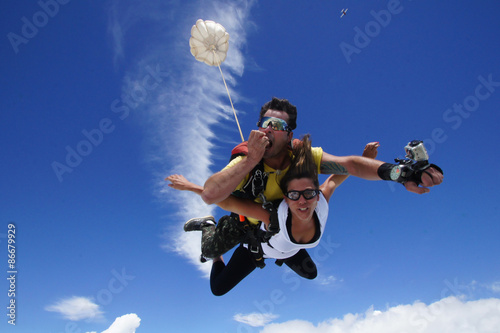 Spoed Foto op Canvas Luchtsport Skydiving tandem happy boy and girl. The instructor eats an apple