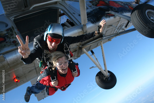 Instructor skydiving jump from the plane and his student shouts.