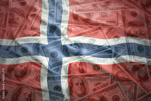 Photo  colorful waving norwegian flag on a american dollar money background