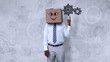 Businessman wearing smiley face box pointing on cogwheel