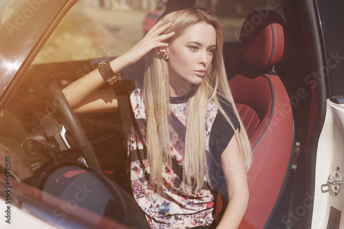 Fototapeta Nice portrait of blonde young woman at the wheel of sport car with red interior, with sunglasses obraz na płótnie