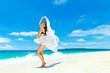 Young beautiful girl in bikini with white cloth on the beach of