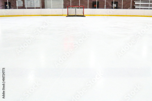 Photo  Perspective of a tiny hockey net across expansive ice at an indoor rink