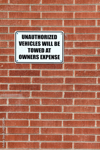 Fotografie, Obraz  Vertical composition of a sign warning that unauthorized vehicles will be towed