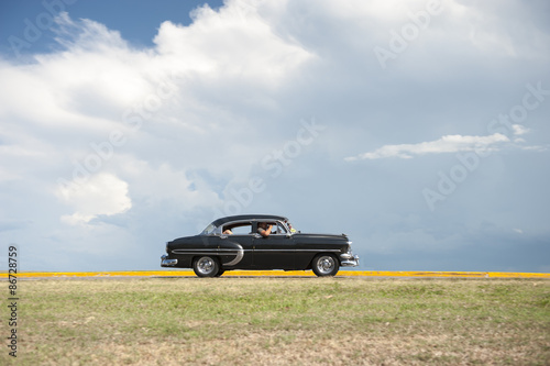 Poster Vintage voitures Classic vintage American car drives along a flat coastal road against a background of tropical clouds