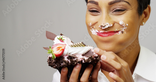 Staande foto Kruidenierswinkel Black woman making a mess eating a huge fancy dessert