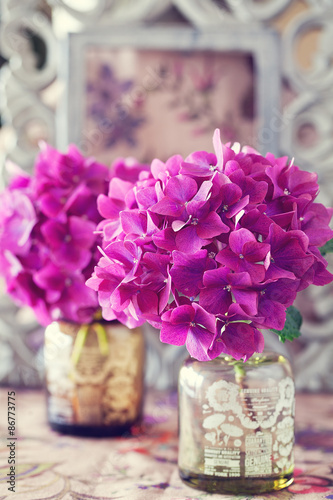beautiful purple hydrangea flowers in a vase on a table .