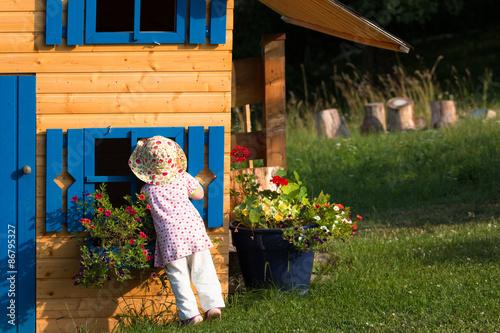 Obraz na plátne Girl looking into wooden playhouse in summer garden
