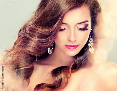 Foto  Schöne Modell Brunette mit dem langen gekräuselten Haar und Schmuck Ohrringe