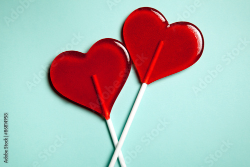 Fotografie, Obraz  Two lollipops. Red hearts. Candy. Love concept. Valentine day.