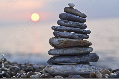 Leinwand Poster Stack of pebbles on beach. Natural background