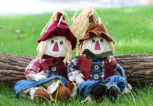 Two Scarecrows Sitting By Log In Grass