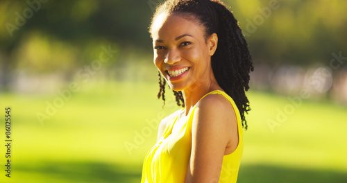 Fototapeta Black woman smiling in a field obraz