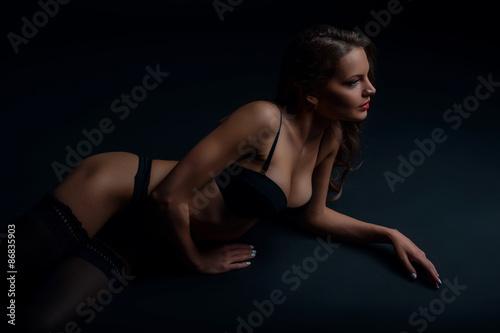 Plakat Atrakcyjna młoda dziewczyna jest relaksująca w ciemnej bieliźnie