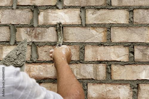 Fotografia, Obraz  Mason applying cement to brick wall