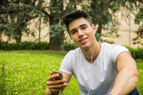 fototapeta na lodówkę Młody człowiek słuchając muzyki w parku
