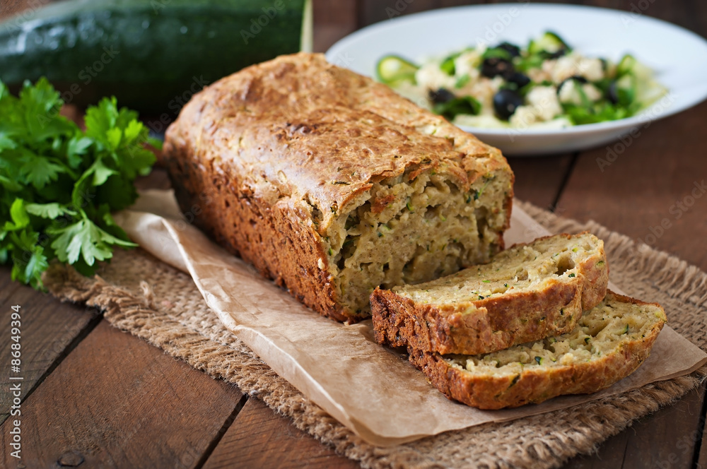 Zucchini bread with cheese on a wooden background