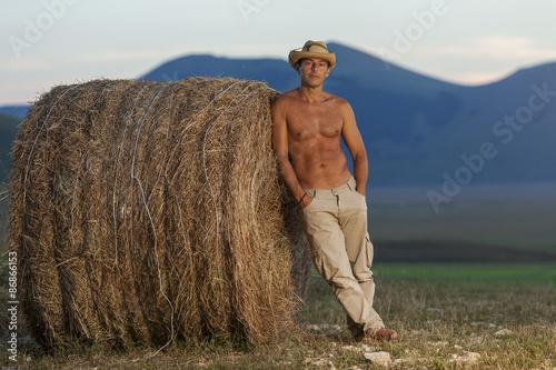 Fotografia  Cowboy a torso nudo su una balla di fieno. Montagne all'orizzonte