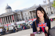 Young Chinese Tourist Holding A Postcard In Trafalgar Square