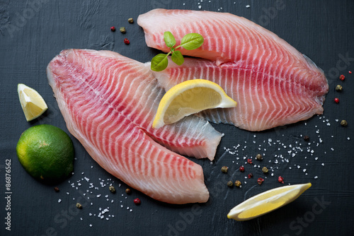 Photo  Fresh tilapia with seasonings, black wooden surface, close-up