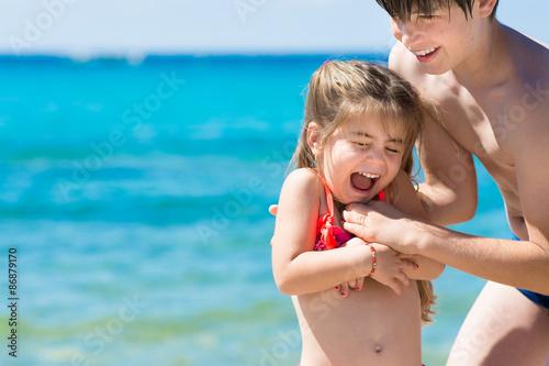 Fotografie, Obraz  Fratello e sorella giocano al mare, mare color turchese come sfondo