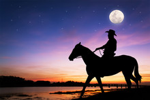 Silhouette Of Cowboy Sitting On His Horse At River Full Moon After Sunset Background