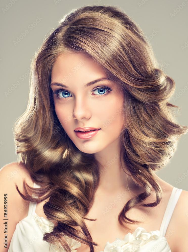 Fotografie, Obraz  Krásná mladá dívka s dlouhými kudrnatými vlasy účes