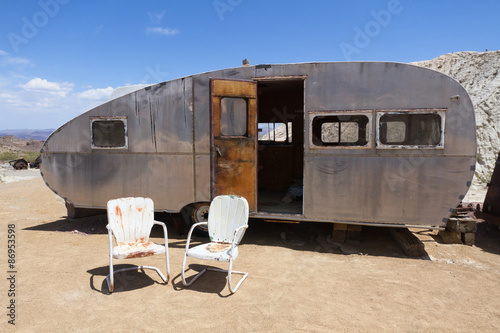 Retro Styled Camping Trailer In Desert Area. Two Old Chairs In Front.