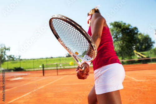 Young woman playing tennis Poster