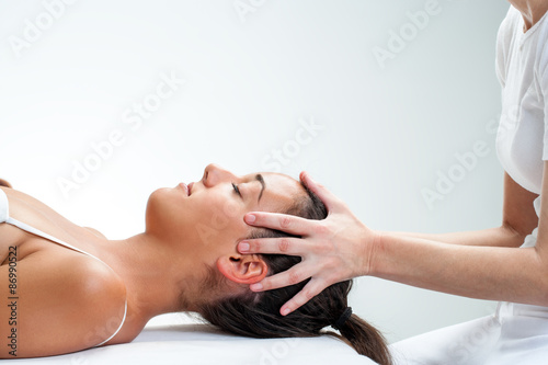 Therapist doing healing osteopathic treatment on woman. Canvas Print