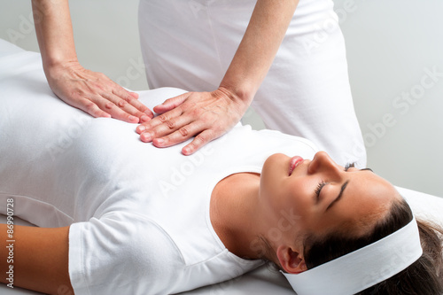 Photo  Therapist pressing with hands on womans chest at reiki session.