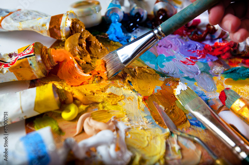 Artist brush mix color oil painting on palette. Abstract art.