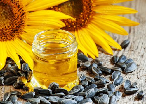 Fototapeta Sunflower oil in the pot, and sunflower seeds on an old wooden b obraz