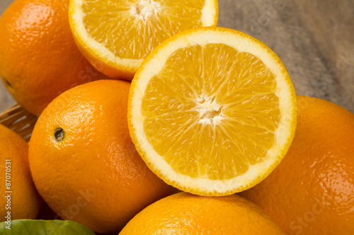 Spoed Foto op Canvas Plakjes fruit Close up of some oranges in a basket over a wooden surface